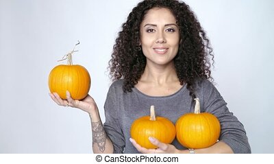 Woman holding ripe orange pumpkins