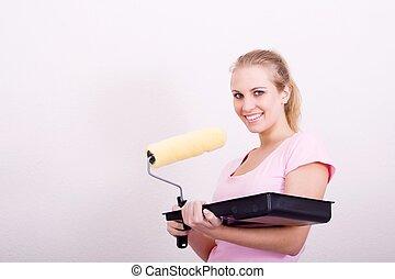 woman holding roller paintbrush