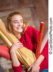 Woman holding rolls of wrapping paper