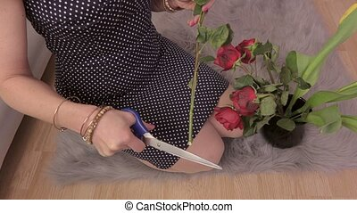 Woman holding rose and scissors