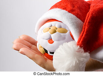 Woman holding Santa Claus in the hand