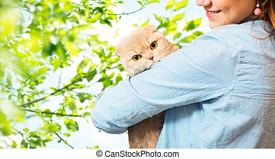 woman holding scottish fold cat over tree