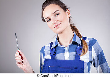 Woman holding screwdriver - Beautiful young woman holding...