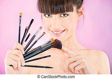 woman holding set of make up brushes