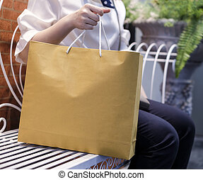 Woman holding shopping bag and sitting on the chair