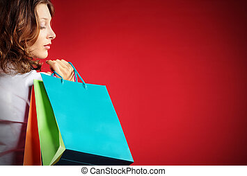 Woman holding shopping bags against a red background