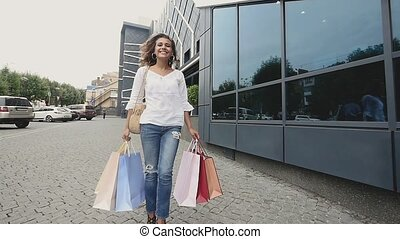 woman holding shopping bags and enjoying the commercial store sales. Successful fashion brunette after buying clothes. slow motion