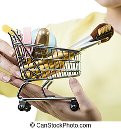 Woman holding shopping cart with make up brushes