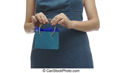 Woman Holding Small Blue Gift Bag - Woman in a blue dress...