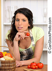 Woman holding small tomato
