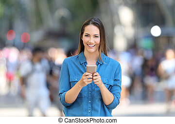 Woman holding smart phone looks at camera