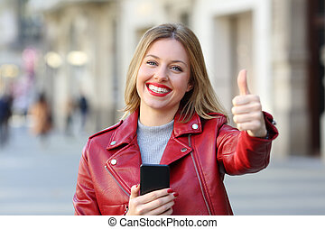 Woman holding smart phone with thumb up on the street