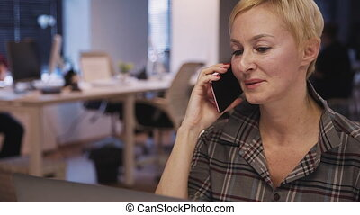 Woman holding smartphone in her hand and talking with...