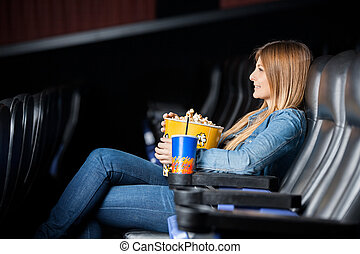 Woman Holding Snacks While Watching Film At Theater