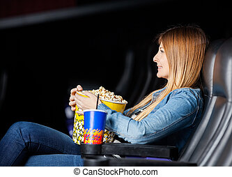 Woman Holding Snacks While Watching Movie At Theater