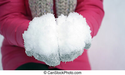 woman holding snow in hands outdoors in winter.