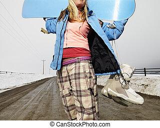 Woman holding snowboard.