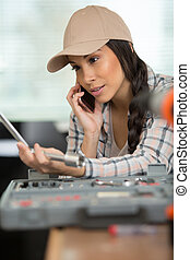 woman holding socket from toolbox and making phonecall