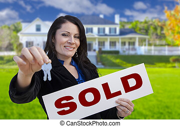 Woman Holding Sold Sign and Keys In Front of House