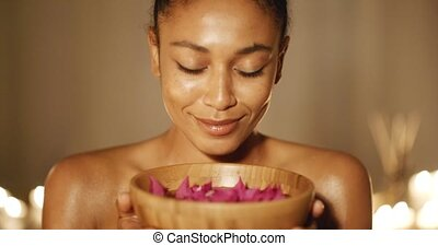 Woman holding spa treatment bowl and smelling aroma in tropical spa