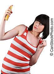 Woman holding sprayer on gray background