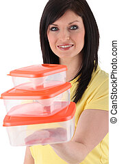 Woman holding stack of plastic food storage