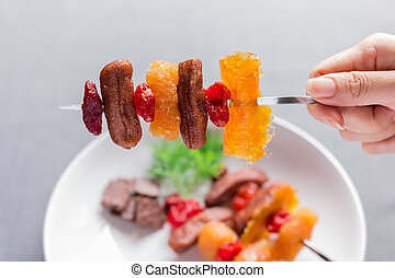 Woman holding stainless steel skewers with dried fruits...
