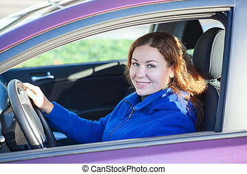 Woman holding steering wheel, smiling at camera, sitting on driver's seat in car