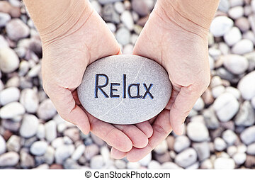 Woman holding stone with the word Relax in her palms