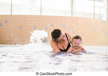 Woman holding sweet baby girl, sitting in a pool.