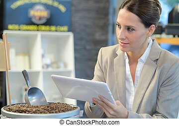Woman holding tablet next to container of coffee beans