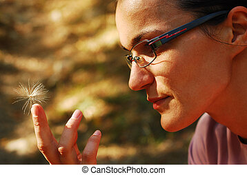 woman holding thistle seed