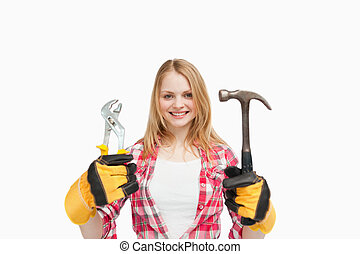 Woman holding tools while smiling