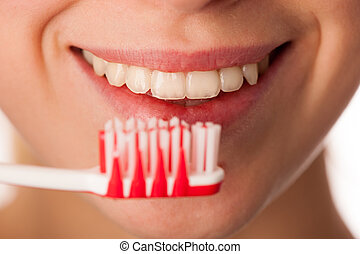 Woman holding toothbrush in front of teeth promoting mouth hygiene for healthy teeth.