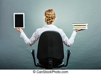 Woman holding traditional book and e-book reader - Ebook vs...