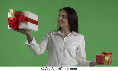 Woman holding two gift boxes in hands against green screen.