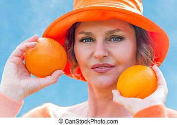 Woman holding  two  oranges