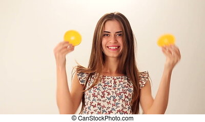 Woman holding two pieces of orange