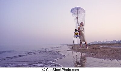 Woman holding white umbrella with long veil poses near picture fixed on easel on sand beach against sea in mist and foggy city