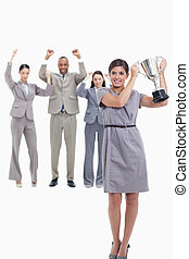 Woman holding up a cup with happy co-workers