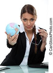 Woman holding up a mini-globe