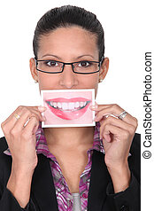 Woman holding up an enlarged picture of her mouth