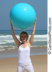 Woman holding up an exercise ball