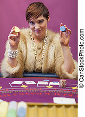Woman holding up chips at poker game