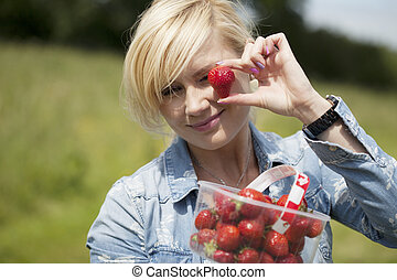 Woman holding up large ripe strawberry