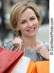 Woman holding up shopping bags