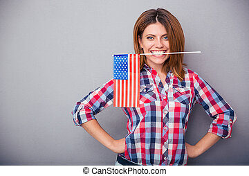 Woman holding USA flag in teeth