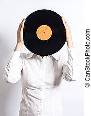 woman holding vinyl record over face