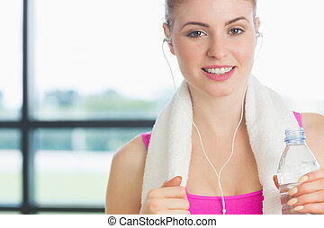 Woman holding water bottle in fitness studio