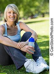 Woman holding water bottle in park